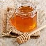 Honigtops mit Honiglöffel auf Holztisch.