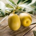 2 Oliven auf einen Holztisch mit Blättern.