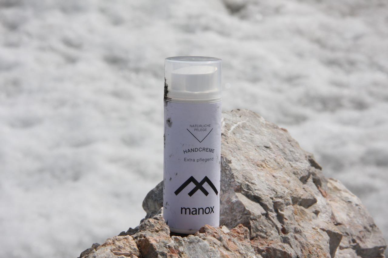 Manox Handcreme auf einen Stein vor einem Schneefeld.