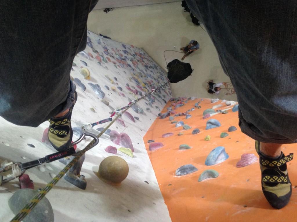 Foto zwischen den Beinen von oben runter auf der Kletterwand.