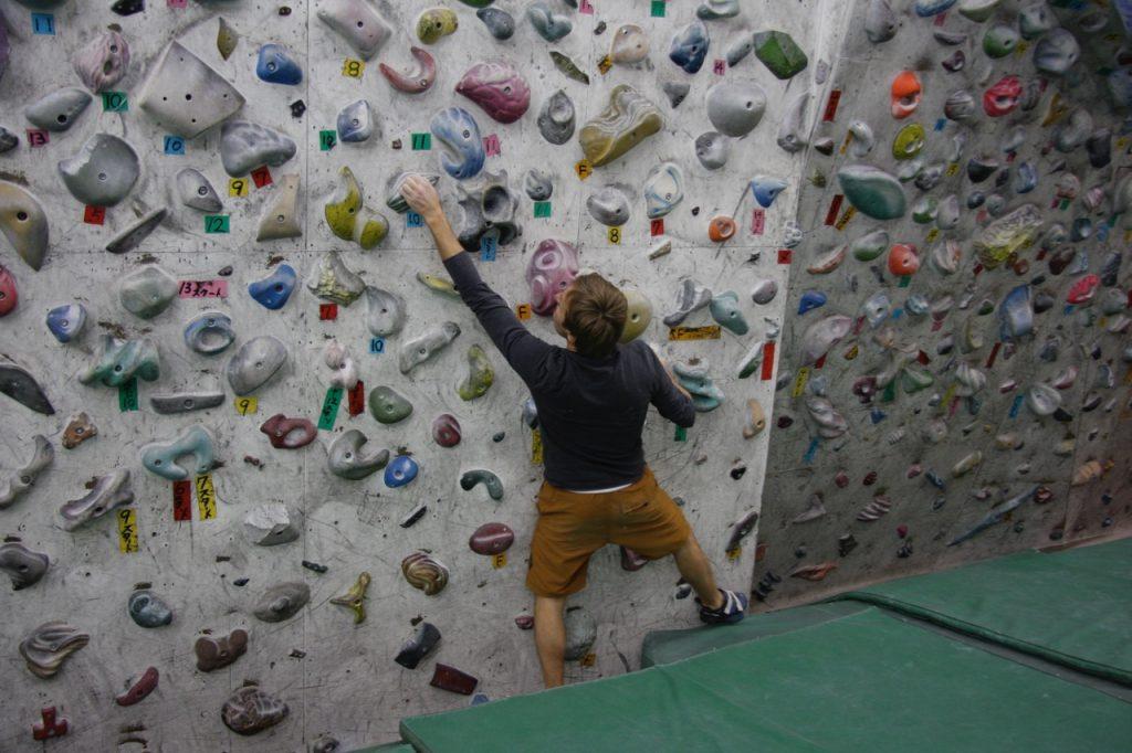 Boulderer auf einer Wand mit vielen Klettergriten