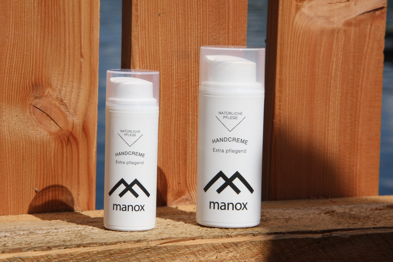 Manox Handcreme groß und klein vor Holzuntergrund