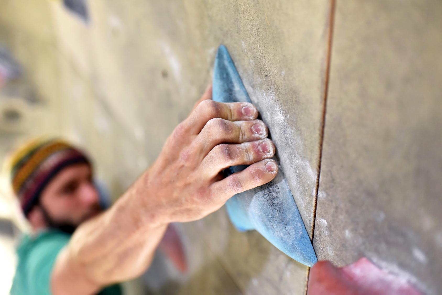 Hand haellt sich an Griff fest, Kletterer in Halle